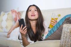 Молодая красивая и счастливая азиатская китайская женщина на ее 20s или 30s лежа на кресле софы живущей комнаты выпивая здоровое  стоковые изображения rf