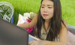 Молодая красивая и счастливая азиатская китайская женщина работая outdoors с кафем предпосылки зеленой травы сети портативного ко стоковые фото