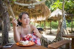 молодая красивая и счастливая азиатская корейская женщина в бикини имея завтрак-обед или завтрак обеда на тропическом пляжном ком Стоковые Изображения RF