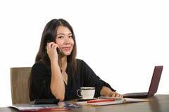 Молодая красивая и счастливая успешная азиатская корейская работа коммерсантки ослабила на говорить стола компьютера офиса усмеха стоковая фотография