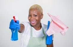 Молодая красивая и счастливая черная Афро-американская женщина используя детержентную бутылку брызга как чистка и стирка оружия у стоковое фото rf