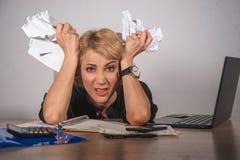 Молодая красивая и усиленная бизнес-леди держа обработку документов отчаянная и разочарованная работа на чувстве стола портативно стоковое фото