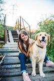 Молодая красивая и усмехаясь девушка играя с собакой Стоковые Изображения RF