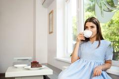 Молодая красивая кавказская дама наслаждается выпить и иметь десерт в современной кофейне в полдень стоковая фотография rf