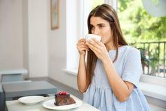 Молодая красивая кавказская дама наслаждается выпить и иметь десерт в современной кофейне в полдень стоковые изображения