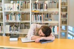 Молодая красивая кавказская девушка отдыхая в библиотеке стоковое фото rf