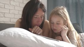 Молодая красивая мать и ее милая дочь делают онлайн покупки на планшете и усмехаться пока лежащ на кровати на сток-видео
