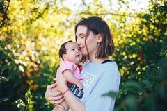 молодая красивая мать с темными волосами держит ее newborn ребёнок стоковые фотографии rf