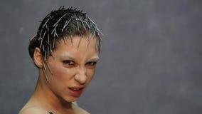 Молодая красивая модель при необыкновенный стиль причёсок представляя для фото в студии видеоматериал