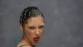 Молодая красивая модель при необыкновенный стиль причёсок представляя для фото в студии акции видеоматериалы