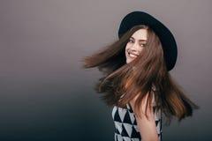 Молодая красивая модная женщина с ультрамодным составом в черной шляпе и стеклах на серой предпосылке Модельная смотря камера, w стоковые изображения rf