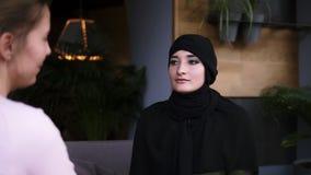Молодая красивая мусульманская женщина в hijab говоря что-то к другой женщине пока сидящ в кафе Диалог Отснятый видеоматериал от акции видеоматериалы