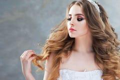 Молодая красивая невеста с роскошными скручиваемостями Стиль причёсок свадьбы с тиарой Стоковая Фотография