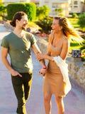 Молодая красивая пара, в влюбленности держа руки, романтичный идти на праздник снаружи, имеющ дату, смотрящ один другого наблюдае Стоковое Изображение RF