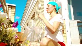 Молодая красивая питьевая вода женщины на балконе после фитнеса или йоги Стоковые Изображения