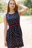 Молодая, красивая, привлекательная женщина в стильном платье, представляя на камере Она смеется над, представляется для камеры, е Стоковая Фотография