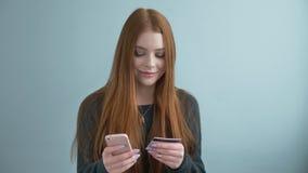 Молодая красивая рыжеволосая девушка делает приобретение онлайн, онлайн-банкинги используя ходить по магазинам smartphone онлайн  сток-видео