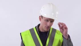 Молодая красивая самоуверенная стойка человека в белой предпосылке и исправлять его шляпа конструкции Стрельба в студии на a сток-видео