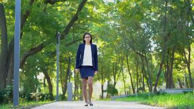 Молодая красивая счастливая бизнес-леди в официальной носке и стеклах идя в зеленый парк самостоятельно Девушка держит путь работ сток-видео