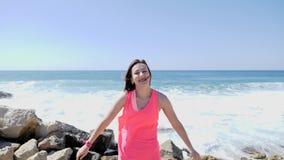Молодая красивая счастливая девушка хлопая в ладоши и скача на скалистый пляж моря с волнами и брызгать воды Ветреный солнечный д акции видеоматериалы
