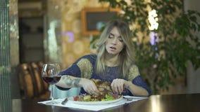Молодая красивая татуированная белокурая девушка в мясе причудливого ресторана обедающего срывая есть с поведением пальцев неумес видеоматериал