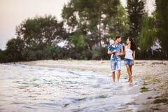 Молодая красивые и стильно одетые мама, папа и дочь людей семьи из трех человек одного года на плечах идти человека стоковое изображение rf