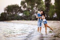 Молодая красивые и стильно одетые мама, папа и дочь людей семьи из трех человек одного года на плечах идти человека стоковая фотография