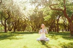 Молодая красная женщина волос мирно размышляя в парке Стоковая Фотография