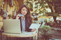 Молодая кредитная карточка проверки бизнес-леди рассчитывать компьтер-книжку Стоковые Фотографии RF