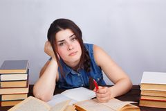 Молодая ленивая пробуренная женщина студента сидя на таблице с текстом bo Стоковое Изображение