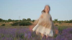 Молодая малая девушка сидит в кустах и счастливо скачет вверх солнце летнего времени природы лаванда цветков заводов наслаждение  видеоматериал