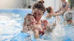 Молодая мама в бассейне играя с ее дочерью младенца в замедленном движении Семья спорт принималась за активный образ жизни видеоматериал