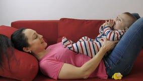 Молодая мама хлопая руки ` s сына младенца на кресле видеоматериал