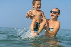 Молодая мать в черных солнечных очках и усмехаясь сыне ребёнка в зеленой бейсбольной кепке играя в море во времени дня Положитель Стоковое Фото