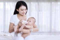Молодая мать давая молоко к ее младенцу дома Стоковое фото RF