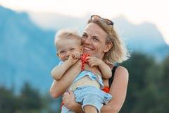 Молодая мать держа ее маленького сына в ее оружиях и они сыграны против фона ландшафта горы стоковая фотография rf