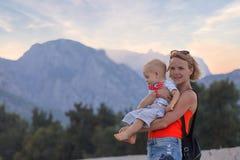 Молодая мать держа ее маленького сына в ее оружиях против фона ландшафта горы стоковое фото