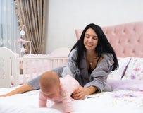 Молодая мать держа ее младенца от вползать прочь стоковое изображение