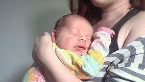 Молодая мать держа ее новорожденный ребенка Милый newborn младенец спать и усмехаясь видеоматериал