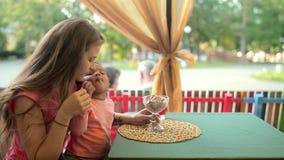 Молодая мать держа маленькую девочку cream льдед еды акции видеоматериалы