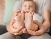 Молодая мать держа ноги ее любящего младенца Стоковые Изображения RF