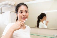 Молодая мать держа сторону зубной щетки к камере Стоковые Изображения