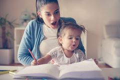 Молодая мать дома наблюдая ее дочь как нарисовать стоковые изображения