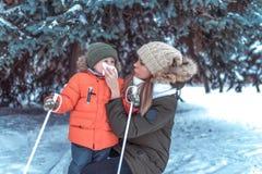 Молодая мать, женщина обтирает ее нос с салфеткой, мальчика 3-4 лет старого сына В зиме в парке снаружи Заботить для стоковые фото