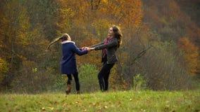 Молодая мать играет с ее маленькой дочерью в водовороте мамы и дочери леса осени вокруг весело, держащ руки акции видеоматериалы