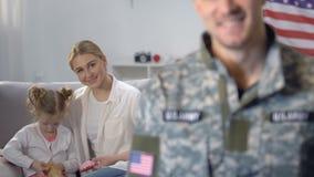 Молодая мать играя с дочерью, смотря военного супруга, оборона семьи сток-видео