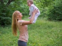 Молодая мать играя с ребёнком внешним в летнем дне Стоковое Фото