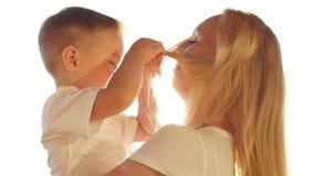 Молодая мать играя с сыном младенца на заходе солнца движение медленное видеоматериал