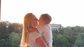 Молодая мать играя с сыном младенца на заходе солнца движение медленное сток-видео