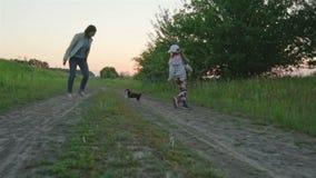 Молодая мать играя с hisdaughter в парке с малым чихуахуа собаки видеоматериал